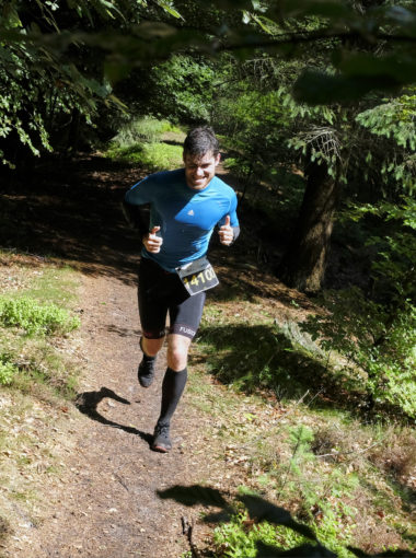 Mand løber i skov, iført sportstøj